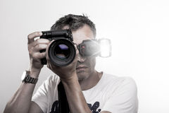 Face shot of a photographer. Frontal portrait of a handsome professional photographer with DSLR camera and speed light on hot show stock photo