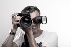 Face shot of a photographer. Frontal portrait of a professional photographer with DSLR camera and speed light on hot show royalty free stock photo