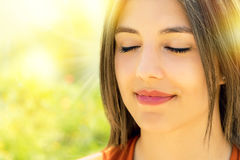 Face shot of relaxed woman meditating outdoors. Close up portrait of attractive relaxed young woman meditating outdoors.Girl with eyes closed against bright stock photography