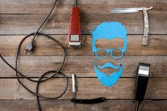 Face silhouette and hair trimmers. Corded electric hair trimmers, straight razors and man face silhouette on the wooden backrgound, close-up. Salon for men royalty free stock image