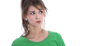 Face of a skeptical young woman in green shirt isolated. Royalty Free Stock Image