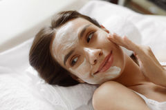 Face Skin Care. Beautiful Woman With Facial Cosmetic Mask At Spa. Face Skin Care. Closeup Of Beautiful Healthy Smiling Woman With White Cosmetic Mask On Her Face Stock Image