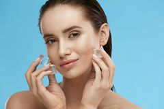 Face Skin Care. Woman Applying Ice Cubes. Beautiful Smiling Girl Doing Icing Facial Treatment On Fresh Healthy Skin. High Quality stock photography