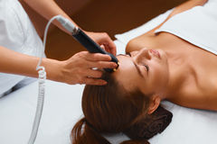 Face skin care. Woman lies on a table in a beauty spa getting a Stock Image
