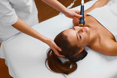 Face skin care. Woman lies on a table in a beauty spa getting a Stock Images