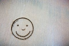 Face smail drawing in the sand . Face smail in the sand on the beach. Travel background royalty free stock image