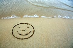 Face smail drawing in the sand at the caribbean beach. Face smail in the sand on the beach. Face smail drawn in the sand with wave rolling Stock Photography