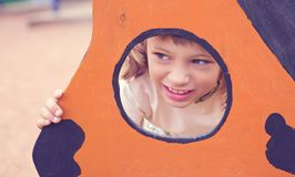 Face of small Caucasian girl looking through a hole in a play equipment outdoors. Orange background. Happy childhood concept. Face of little Caucasian girl stock photos