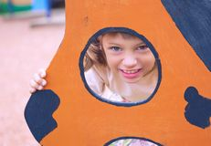 Face of small Caucasian girl looking through a hole in a play equipment outdoors. Orange background. Happy childhood. Face of little Caucasian girl looking stock images