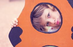 Face of small Caucasian girl looking through a hole in a play equipment outdoors. Orange background. Happy childhood. Face of little Caucasian girl looking royalty free stock photos