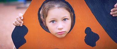 Face of small Caucasian girl looking through a hole in a play equipment outdoors. Orange background. Happy childhood. Face of little Caucasian girl looking royalty free stock images