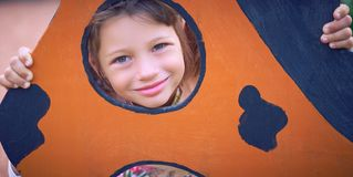 Face of small Caucasian girl looking through a hole in a play equipment outdoors. Orange background. Happy childhood. Face of little Caucasian girl looking royalty free stock image