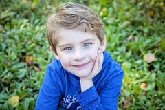 Face of smiling happy boy outside. Face of smiling, happy five year old boy with blue eyes outside sitting in green grass royalty free stock images