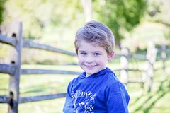 Face of smiling happy boy outside. Face of smiling, happy five year old boy with blue eyes outside sitting in backyard with split rail fence in background royalty free stock photo