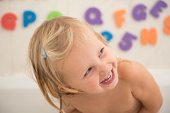 Face of a smiling little girl in the bathroom. Smiling  girl in bathroom with colorful foam letters and numbers in background.Water fun for kids Royalty Free Stock Photos