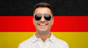 Face of smiling man in sunglasses over german flag Stock Photography