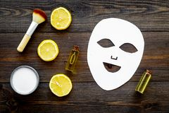 Face spa products. Facial mask, cream, oil, brush near lemon slices on dark wooden background top view.  royalty free stock photos