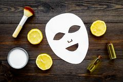 Face spa products. Facial mask, cream, oil, brush near lemon slices on dark wooden background top view.  stock image