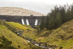 The face of the Spelga dam in the Mountains of Mourne in County down northern Ireland with the overflow sluice gates open in mid J. Anuary 2018. This dam is a Royalty Free Stock Images