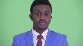 Face of stressed young African businessman looking bored and tired. Studio shot of young African businessman with Afro hair wearing suit against chroma key with stock video