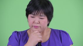 Face of stressed young overweight Asian woman thinking and looking down
