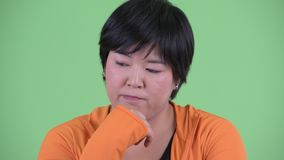 Face of stressed young overweight Asian woman thinking and looking down. Studio shot of young beautiful overweight Asian woman ready for gym against chroma key stock video footage