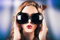 Face of a surprised pinup girl in funny sunglasses Royalty Free Stock Photo