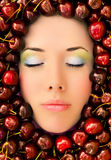 Face surrounded by fruit. Beautiful young woman's face with eyes closed surrounded by ripe red cherries Royalty Free Stock Photo