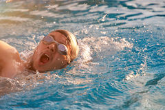 Face of swimming man. In pool blue water close up. Man breath while swim Royalty Free Stock Photo