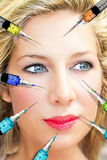 Face with syringes. Face of a beautiful woman with doctors hand and syringe royalty free stock photography