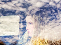 The face of a teen girl and clouds reflected in a truck window Stock Images