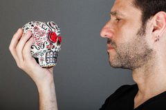 Face to Face with death. A man with a skull on your hand, looking in frontwards Stock Photography