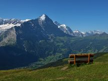 Face To Face With The Eiger. Wooden bench opposite of the Eiger. Village named Grindelwald, travel destination stock photos