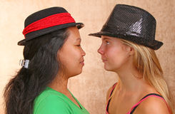 Face To Face Girls. Two Girls Looking Close Up Eye To Eye With Costume Hats Royalty Free Stock Images