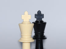 Face to face - two kings, black and white plastic chess pieces, white background Stock Photo