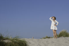 A face to the sun. The taking a sunbath girl standing on the sand looking up stock photo