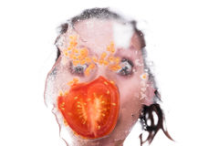 Face with tomato behind a pane. Funny female face with tomato behind a pane, studio shot Royalty Free Stock Photo