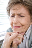 Face of upset elderly woman with eyes closed. Face of upset elderly woman in 70s with eyes closed royalty free stock image