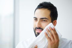 Face Washing. Happy Man Drying Skin With Towel.  royalty free stock photo