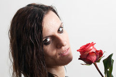 The face of the wet woman and a rose. Woman's face with drops of water and a red rose Stock Images
