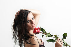 The face of the wet woman and a rose. Woman's face with drops of water and a red rose Royalty Free Stock Image