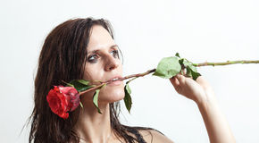 The face of the wet woman and a rose. Woman's face with drops of water and a red rose Stock Photo