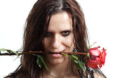 The face of the wet woman and a rose. Woman's face with drops of water and a red rose Royalty Free Stock Images