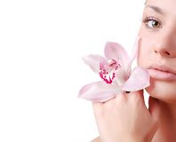 Face of woman. Face of beautiful young woman with delicate orchid Stock Photo