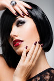 Face of a woman with beautiful dark nails and Royalty Free Stock Photos