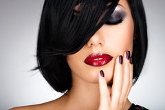 Face of a woman with beautiful dark nails and red lips royalty free stock images