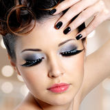Face of woman with fashion eye makeup. Portrait of the glamour woman with black nails and fashion eye makeup stock photo