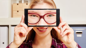 Face of a woman with glasses on a smartphone Stock Photo
