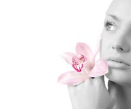 Face of woman and orchid Stock Photos