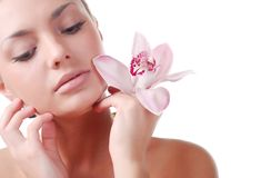 Face of woman orchid. Face of beautiful young woman with delicate orchid Royalty Free Stock Photo
